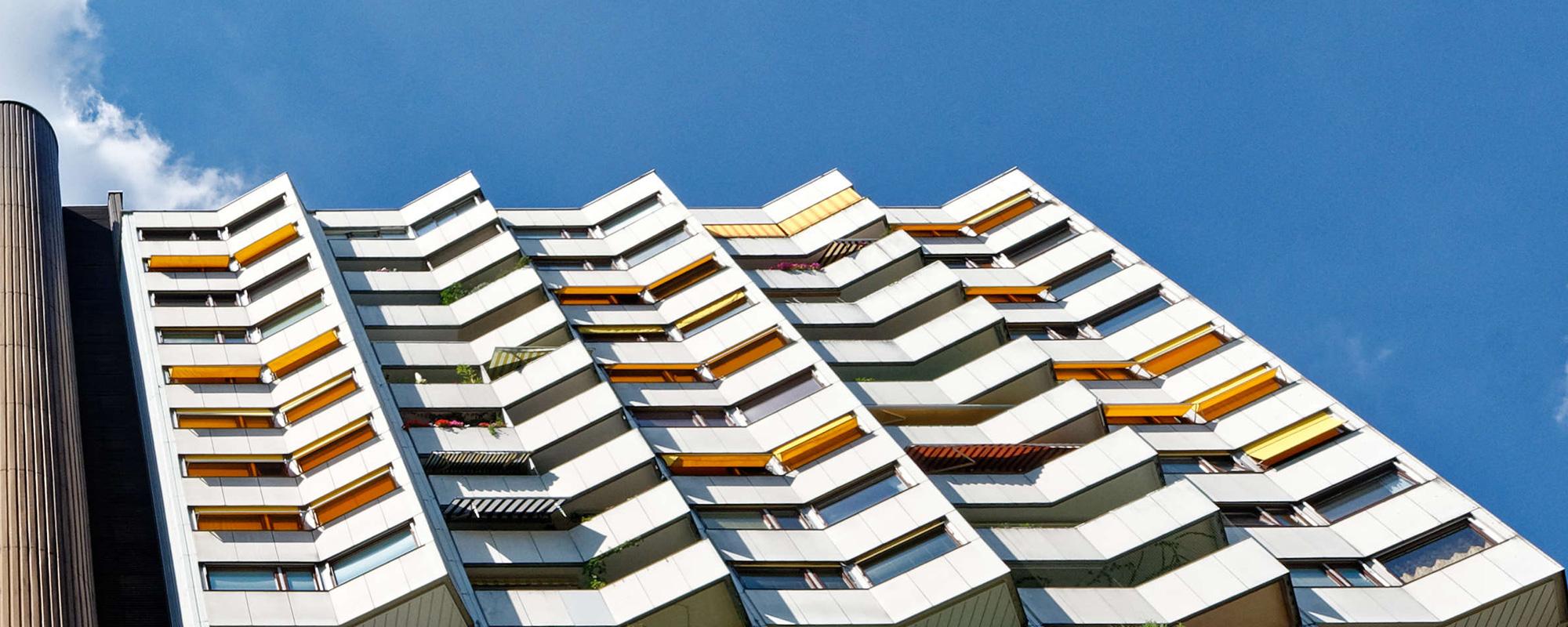 brauner Liftturm und weiße Fassade des Wohnparks mit Loggien und orangen Markisoletten im Sommer